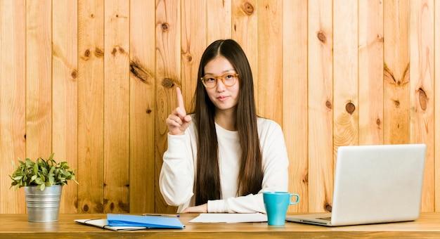 指でナンバーワンを示す彼女の机で勉強して若い中国人女性。