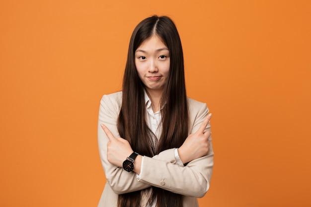 Молодой бизнес китаянка указывает в сторону, пытается выбрать один из двух вариантов.