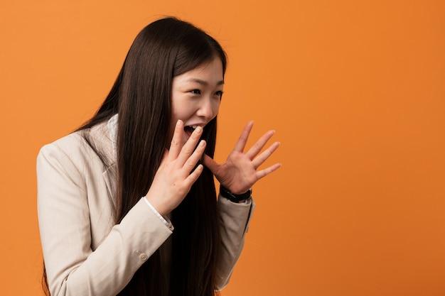 Молодой бизнес китаянка кричит громко, держит глаза открытыми и руки напряжены.