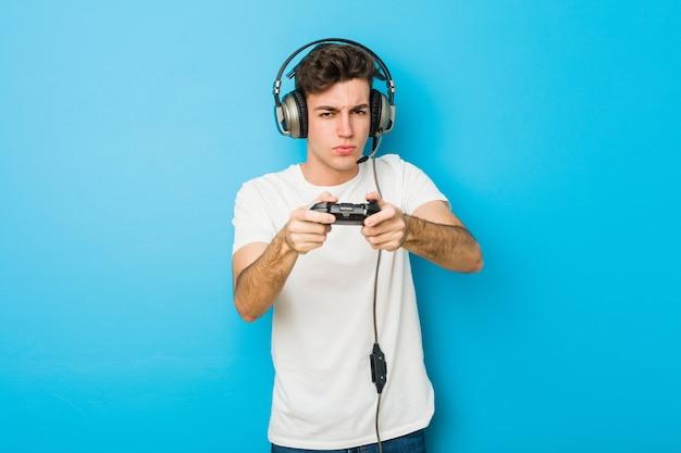ヘッドフォンとゲームコントローラーを使用してティーンエイジャーの白人男性