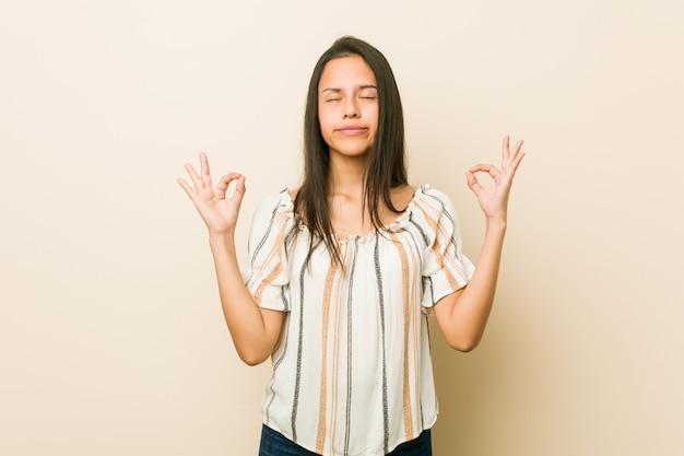 Молодая испанская женщина расслабляется после тяжелого рабочего дня, она выполняет йогу.