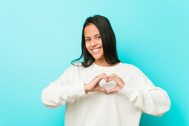Молодая милая испанская женщина усмехаясь и показывая форму сердца с руками.