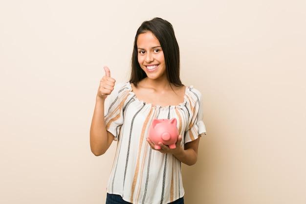Молодая испанская женщина держит копилку, улыбаясь и поднимая палец вверх