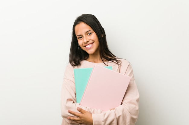 幸せ、笑顔、陽気ないくつかのノートを保持している若いヒスパニック系女性。