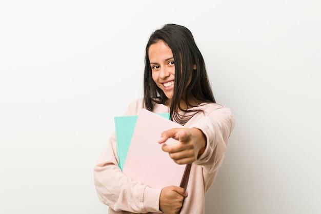 いくつかのノートを前に指している陽気な笑顔を保持している若いヒスパニック系女性。