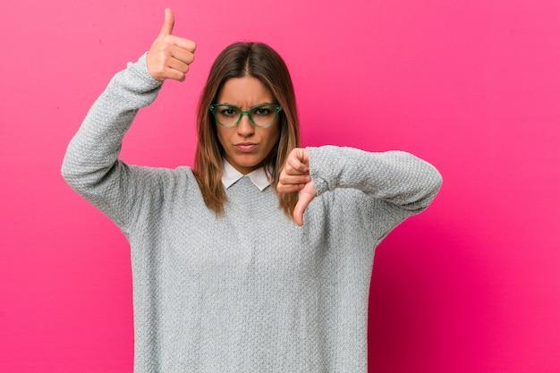 若い正真正銘のカリスマ的な本物の女性の壁に親指と親指を表示、難しい選択の概念