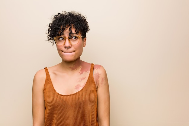 皮膚の出生マークを持つ若いアフリカ系アメリカ人女性は混乱し、疑わしく不安を感じています。