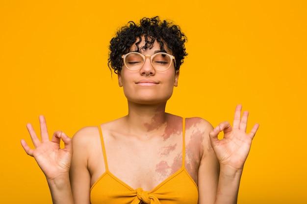 Молодая афро-американская женщина с отметкой рождения кожи ослабляет после тяжелого рабочего дня, она выполняет йогу.