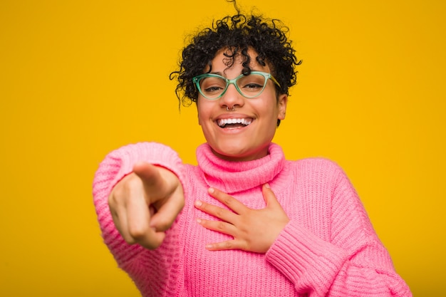 Молодая афро-американская женщина нося розовый свитер указывает с пальцем большого пальца прочь, смеяться над и беспечальным.