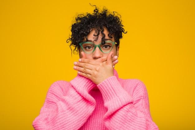 Молодой афроамериканец женщина, одетая в розовый свитер шокирован, охватывающих рот руками.