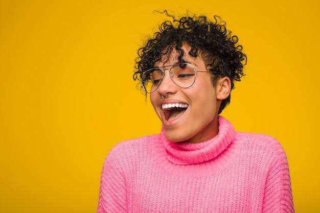 Молодая женщина афроамериканцев, носить розовый свитер, будучи шокирован из-за чего-то она видела.