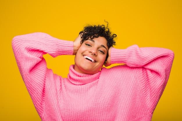 Молодая афро-американская женщина нося розовый свитер смеется радостно держа руки на голове. концепция счастья.