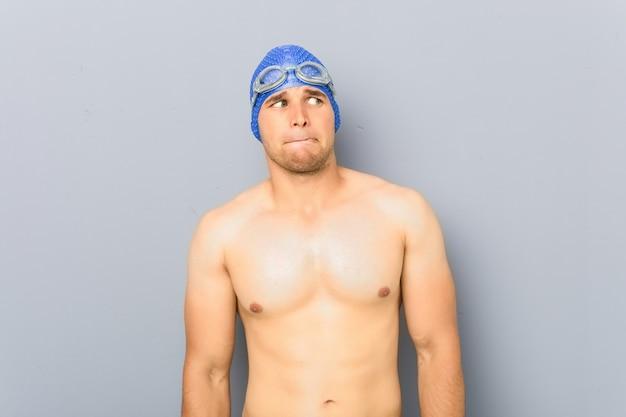 若いプロの水泳選手の男性は混乱し、疑わしく不安を感じています。