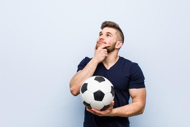 疑わしいと懐疑的な表情で横に見ているサッカーボールを保持している若い白人男。