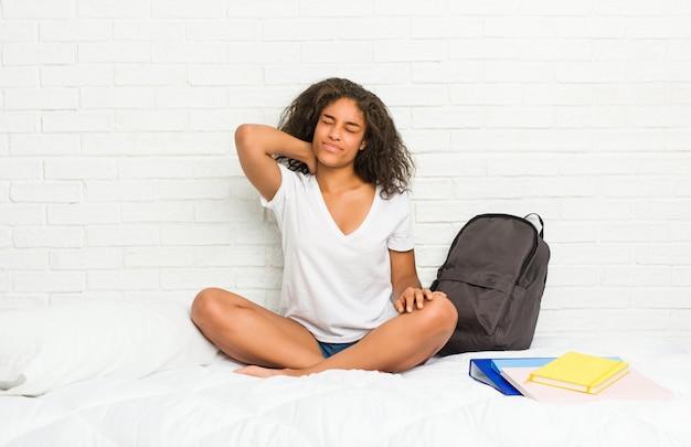 座りがちな生活のため首の痛みに苦しんでいるベッドの上の若いアフリカ系アメリカ人学生女性。