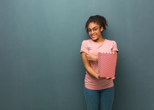 笑顔と側を指している若い黒人女性。彼女はポップコーンのバケツを持っています。