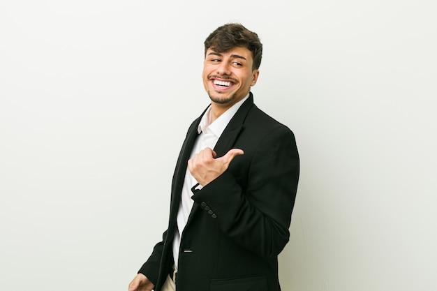 Молодой бизнес испаноязычное человек указывает пальцем в сторону, смеется и беззаботный.
