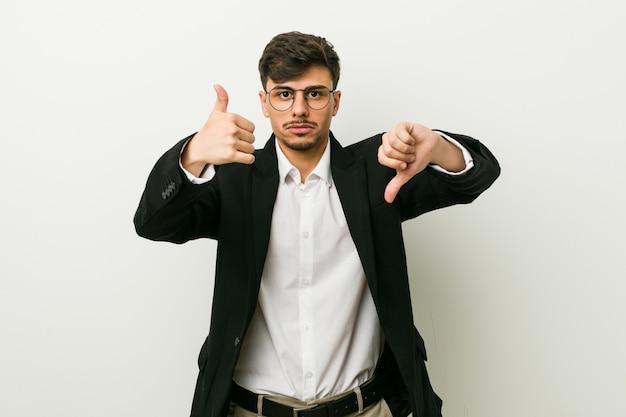 若いビジネスヒスパニック系男性親指と親指を表示、難しいコンセプトを選択
