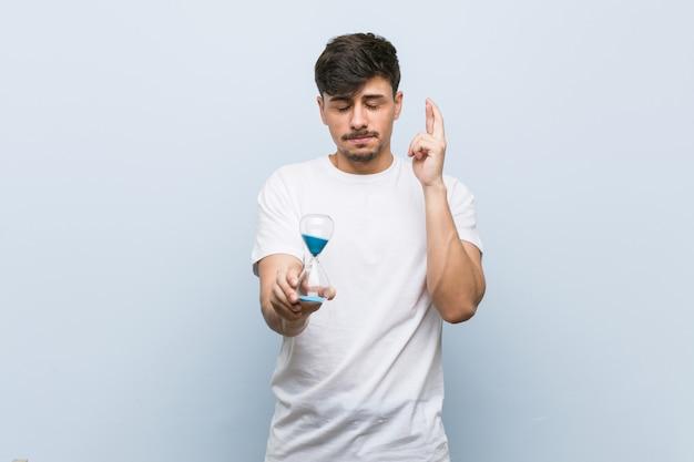 Молодой испаноязычное мужчина держит песочные часы скрещивания пальцев для удачи