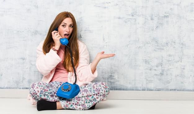 Молодая кавказская женщина держа стационарный телефон впечатлила держащ космос экземпляра на ладони.