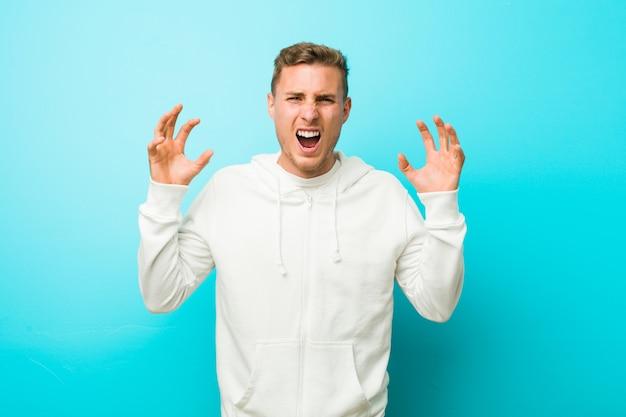 Молодой человек кавказской спорта кричать от ярости.