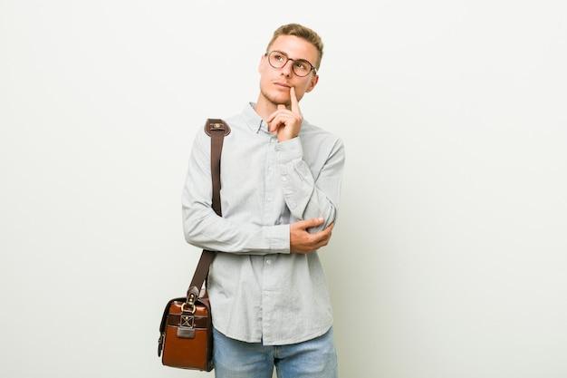 疑わしいと懐疑的な表情で横に探している若い白人ビジネスマン。