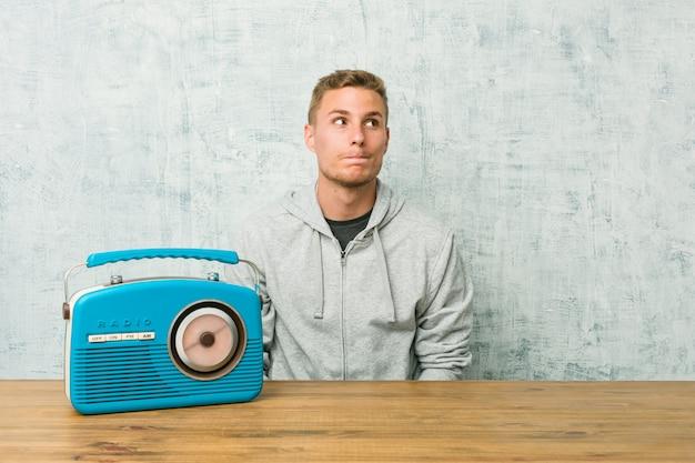ラジオを聞いている若い白人男性は混乱しており、疑わしく不安を感じています。