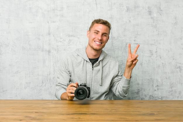 指で平和のシンボルを示すうれしそうな屈託のないテーブルにカメラを持って若い写真家。