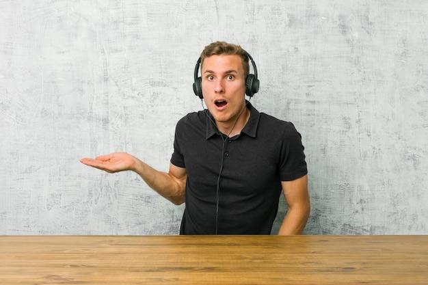 ヘッドフォンで音楽を聴く若い白人男は、手のひらにコピースペースを保持していることに感銘を受けました。