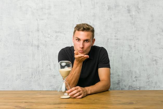 Молодой человек держит песок таймер на столе, складывая губы и держа ладони, чтобы отправить воздушный поцелуй.