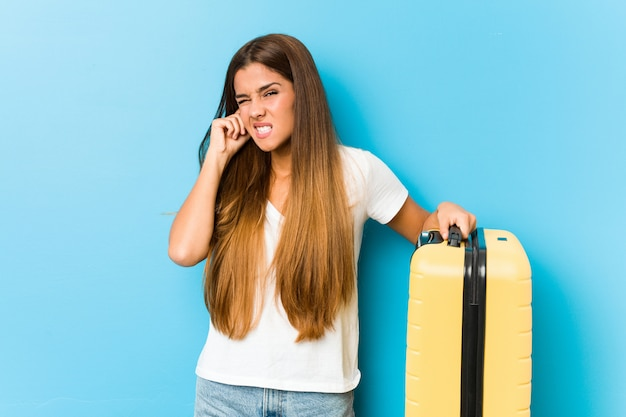 手で耳を覆う旅行スーツケースを保持している若い白人女性。