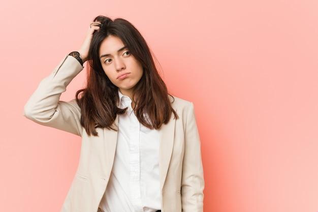 Молодая брюнетка бизнес женщина против розовой стены в шоке, она вспомнила важную встречу.