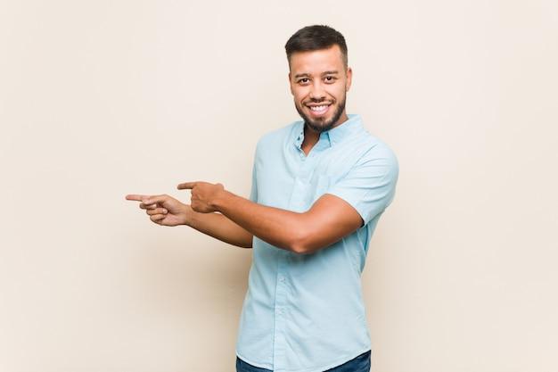 南アジアの若い男は、人差し指を指さして興奮しています。