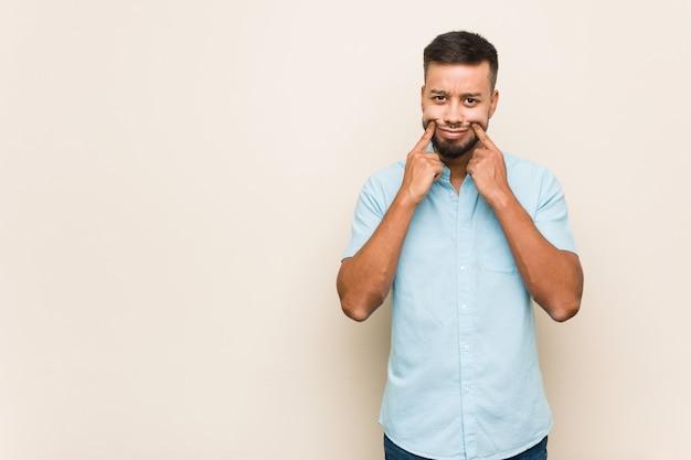 Молодой южноазиатский мужчина сомневается между двумя вариантами.