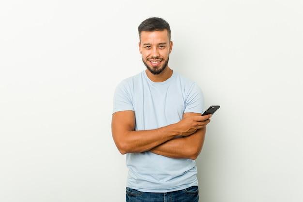 Человек молодой смешанной гонки азиатский держа телефон счастливый, усмехаться и жизнерадостный.