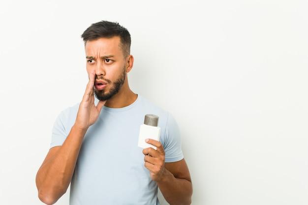 Молодой южноазиатский мужчина держит крем после бритья, рассказывает секретные горячие новости о торможении и смотрит в сторону