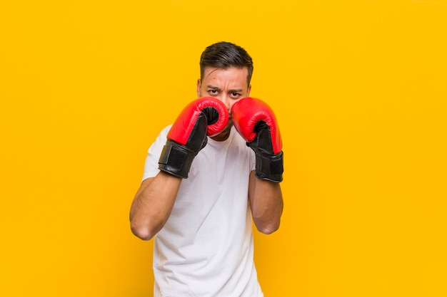 Молодой южноазиатский боксер человек в красных перчатках.