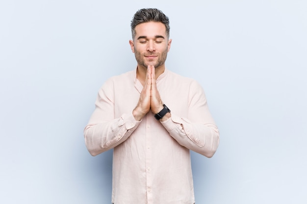 Молодой красивый крутой человек, держась за руки в молитве возле рта, чувствует себя уверенно.