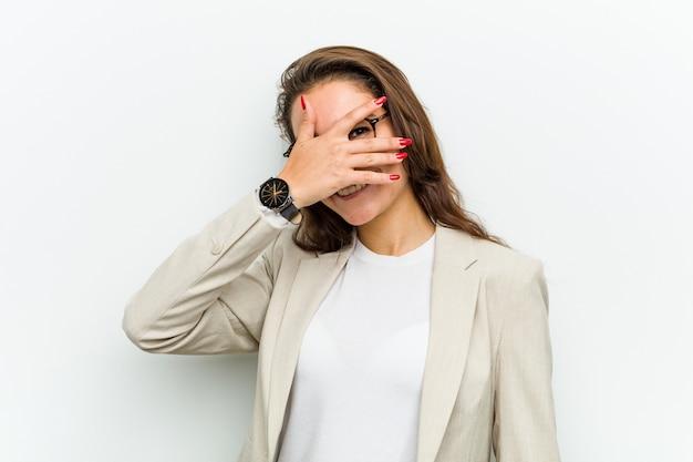 若いヨーロッパビジネスの女性は、彼女の指をカメラで点滅し、彼女の顔を覆って恥ずかしい。