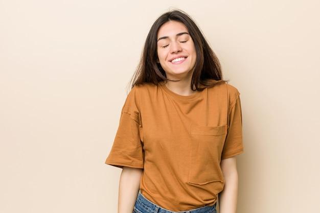 Молодая брюнетка женщина по-бежевски смеется и закрывает глаза, чувствует себя расслабленной и счастливой.