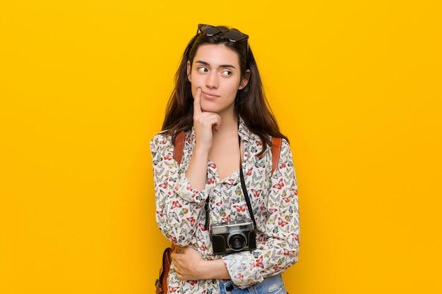疑いと懐疑的な表情で横に探している若いブルネット旅行者女性。
