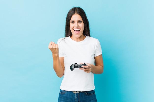 屈託のない、興奮を応援するゲームコントローラーを保持している若い白人女性。勝利のコンセプト。