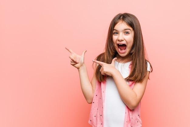 Милая маленькая девочка, указывая указательными пальцами на копией пространства, выражая волнение и желание.