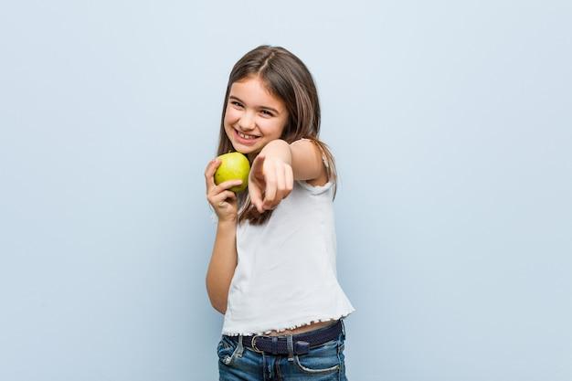 正面を指している青リンゴ陽気な笑顔を保持している白人少女。