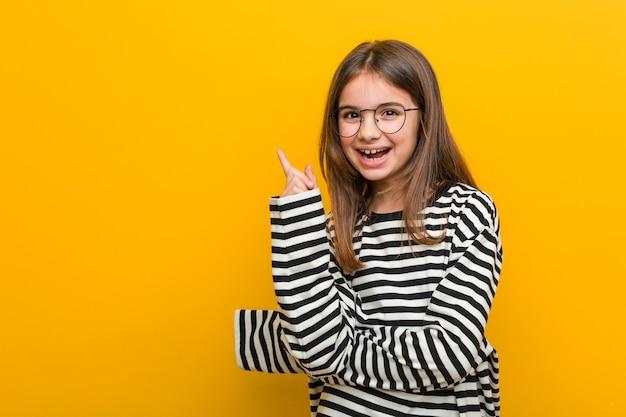 人差し指で離れて元気に笑っている白人のかわいい女の子。