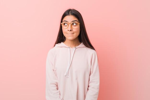 カジュアルなスポーツを着ている若いかなりアラブの女性は混乱しているように見え、疑わしく、自信がありません。