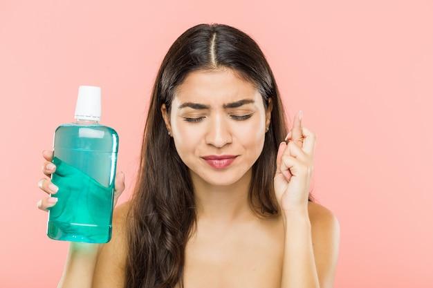 Молодая индийская женщина держа пальцы скрещивания бутылки полоскания рта для иметь удачу