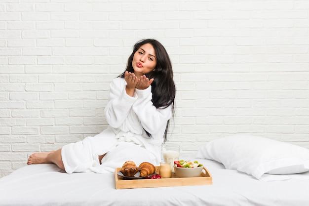Молодая соблазнительная женщина, принимая завтрак на кровати, складывая губы и держа ладони, чтобы отправить воздушный поцелуй.