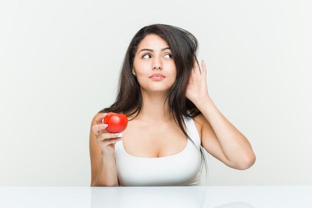 Молодая испанская женщина держа томат пробуя слушать сплетню.