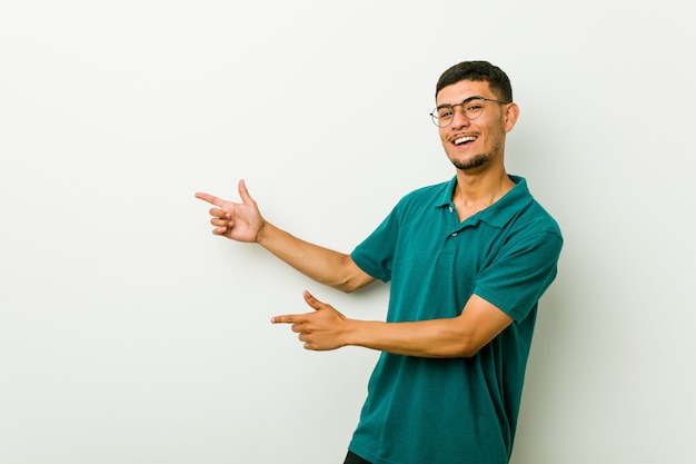 Молодой латиноамериканский человек взволнован, указывая указательными пальцами прочь.